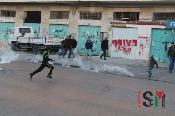 A boy runs after tear gas canister and throws it back