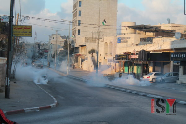 Tear gas fired by Israeli forces fills the street in Bethlehem