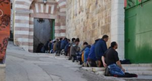 Palestinian men and boys, praying outside al-Ibrahimi mosque
