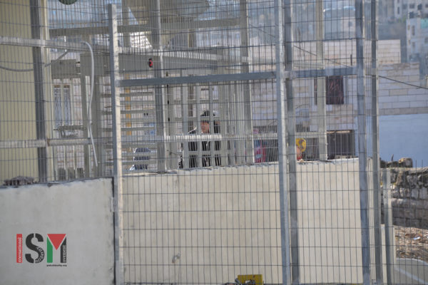 Several Palestinian are standing in line at the entry of the checkpoint, as israeli forces stand by and do nothing.