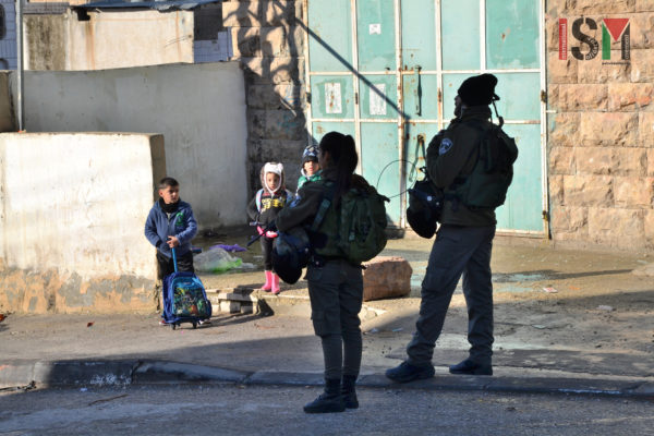 A group of frightened palestinian school children are standing by, as Israeli forces invaded the palestinian neighborhood of Salaymeh.