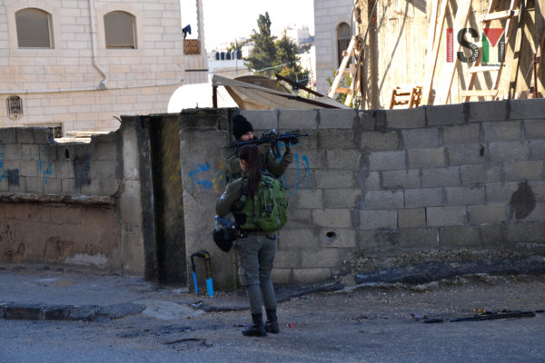Israeli soldier, carrying weapon with live ammunition, pointed his weapon several times at a large group of school children, standing outside of their school.