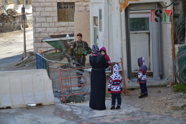 Israeli Soldier checking ID and searching the bag of a Palestinian woman, who was bringing her children to school.