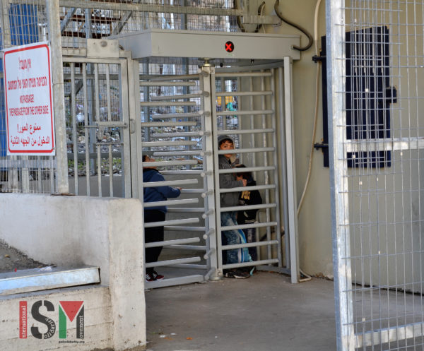 "A group of Palestinian school children exiting the checkpoint, were locked inside and kept waiting. When the soldier who was suppose to operate the checkpoint was confronted by international activists, her response was: ""I don't care. It's my job."""