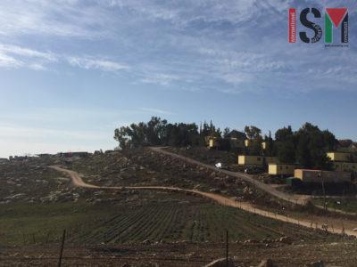 Umm al-Khair (at left) next to the illegal settlement of Carmel