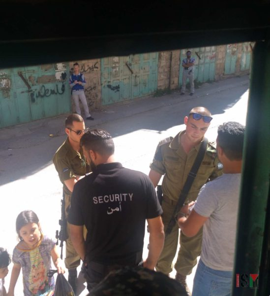 An Israeli commander talks to residents of the Zahida family on the doorstep before entering the house