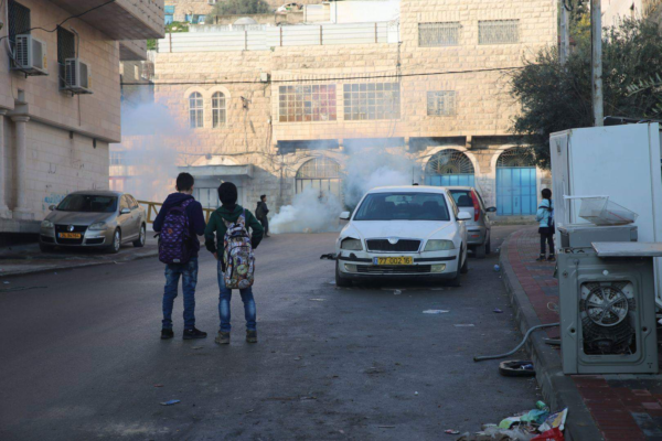 Palestinian children watch as tear gas floods the streets of Qeitun outside of their school