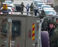 Soldiers arresting 14-year old Ahmer Eqneibi