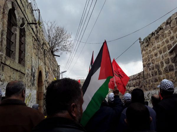 Palestinians marching towards a gate that closes off Shuhada Street, Feb 22, 2019