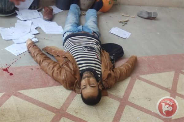 Yasser Fawzi Shweiki lies on the ground after being shot by the Israeli soldiers. Dozens of the court documents he was delivering can be seen scattered around his body.