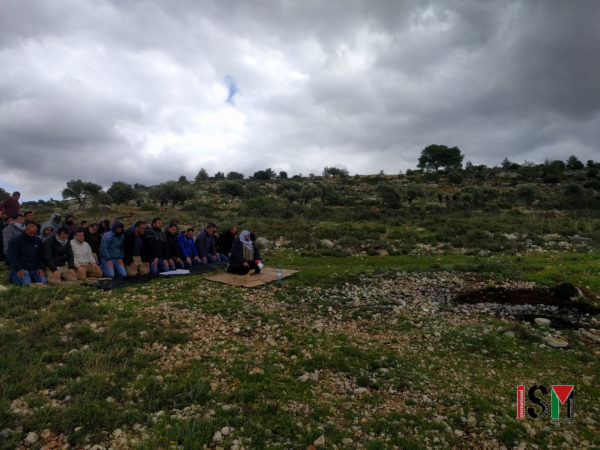 photo of Border Police standing over Palestinians during afternoon prayers on hillside