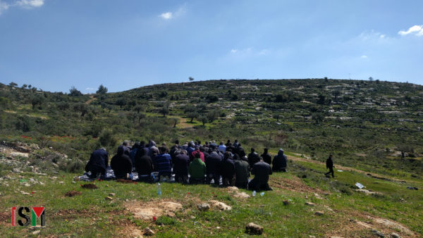 Palestinian demonstrators are kneeling down in prayer on a rocky hill