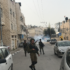 Soldiers invade Al-Khalil, bombarding the city with tear gas and stun grenades. Tear gas is seen in the background.