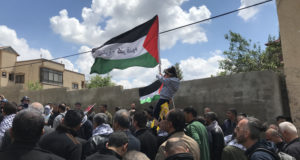 Protesters gather, a Palestinian flag flying, little girl on her fathers shoulders.