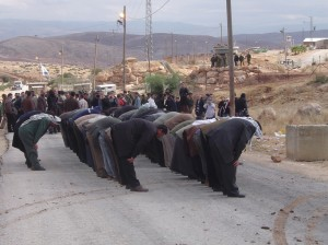 Local Muslims pray near the checkpoint