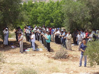 villagers stop to pray on their land as soliders shoot and launch tear gas canisters in the area. Nine people were injured in the demonstration.